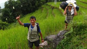 Head Cook Manbakta, and Porter Suriya, navigating a mountainside rice paddy